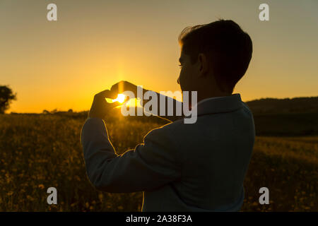 Boy making a heart shape with his hands at sunset, Spain - Stock Photo
