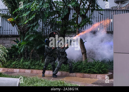 Hong Kong, China. 6th Oct, 2019. Riot place fire teargas near Central Government Complex of Hong Kong. It was the second day after Hong Kong's government invoked emergency powers to enact a ban on wearing face masks in public on Friday October 4th. Violence continued throughout Hong Kong as protesters set fires and vandalized subway stations, restaurants, banks and many other public facilities. Credit: Keith Tsuji/ZUMA Wire/Alamy Live News - Stock Photo