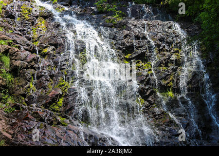 Close up of a powerful mountain waterfall cascading down the rocky, red cliff covered by green and golden sunlit moss - Stock Photo
