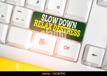 Writing note showing Slow Down Relax Destress. Business concept for calming bring happiness and put you in good mood White pc keyboard with note paper - Stock Photo