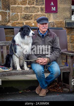 Man with dog sat on wooden bench, Masham Sheep Fair - Stock Photo