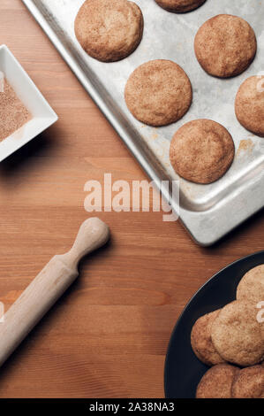 Snickerdoodles cookies (or sugar cookies) on a baking tray and a plate on wood table with a bowl full of sugar and cinnamon and a rolling pin. Vertica - Stock Photo