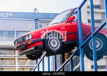 A red BMW car hangs precariously off the roof of a building, as if it had just broken through as the result of an accident, Rotterdam, Netherlands. - Stock Photo