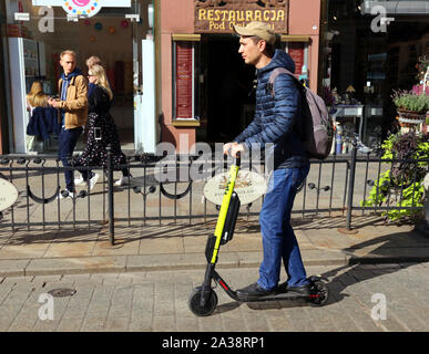 Cracow. Krakow. Poland. Young man riding electrik scooter on Grodzka Str. center of the Old Town. - Stock Photo