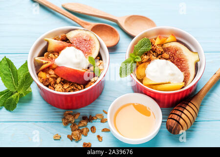 Granola with fruits and greek yogurt on blue background. Closeup view. Healthy breakfast or snack food - Stock Photo