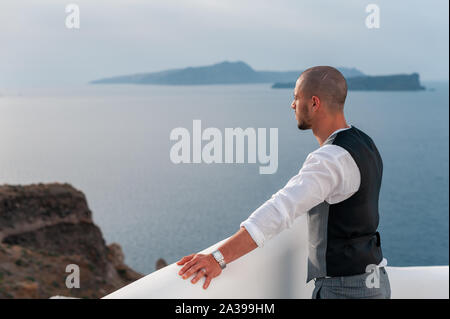 happy stylish groom smiling on background blue sea and sky in island Santorini. Young groom on the background of sea and architecture, Santorini island Greece. - Stock Photo