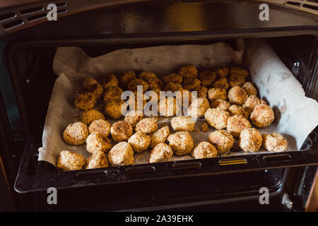 Potato nuggets in an oven, freshly baked - Stock Photo