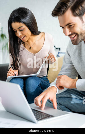 african american woman doing paperwork and handsome man using laptop in apartment - Stock Photo