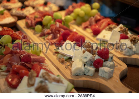 The Hague, Netherlands - november 30 2018 : a cheese wooden platter with fruits and meats, nuts and other healthy food on it. - Stock Photo