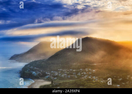 Range of gum-tree covered hills on South Coast off Sydney part of Grand Pacific Driver scenic route with famous Sea Cliff Bridge at sunset from elevat - Stock Photo
