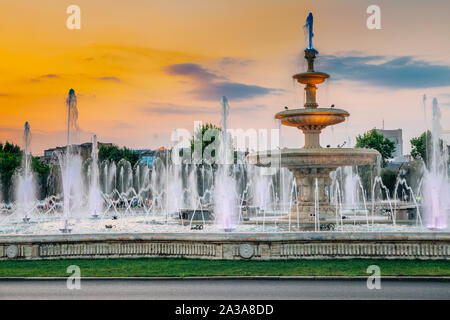 Fountains with sunset at Unirii Square in Bucharest, Romania - Stock Photo