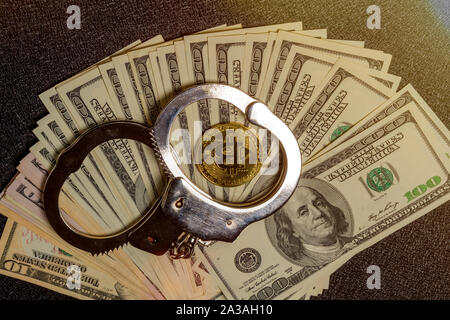 Handcuffs on hundred dollar bills and a gold bitcoin coin. Top view - Stock Photo