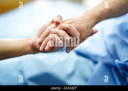 Holding Touching hands Asian senior or elderly old lady woman patient with love, care, helping, encourage and empathy at nursing hospital ward : healt
