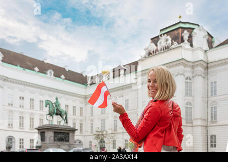 A young girl stands with the flag of Austria against the background of the Austrian National Library in Vienna. - Stock Photo