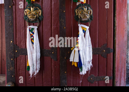 Braided tassels representing prayer flags for good luck hang on the door to Norbulingka, the former summer palace of the Dali Lama in Lhasa, Tibet. - Stock Photo