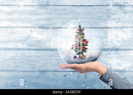 Human hand holding decorated Christmas tree with colorful lights and ornaments in the glass ball ornament over wooden wall background - Stock Photo