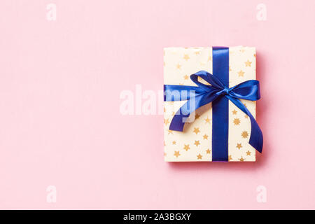 wrapped Christmas or other holiday handmade present in paper with blue ribbon on pink background. Present box, decoration of gift on colored table, to - Stock Photo