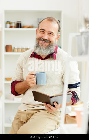Portrait of bearded senior man smiling cheerfully at camera while reading book with cup of coffee in morning - Stock Photo