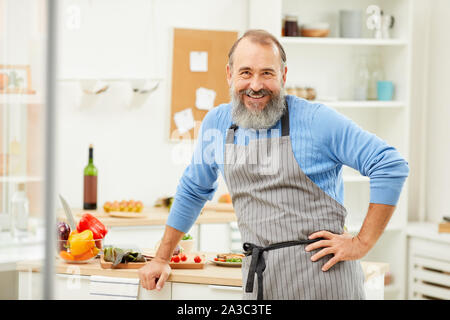Waist up portrait of bearded senior man wearing apron looking at camera cheerfully while cooking at home, copy space - Stock Photo