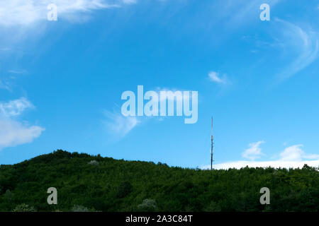 metal tower with GSM antenna on top of green forest hill - copyspace - Stock Photo