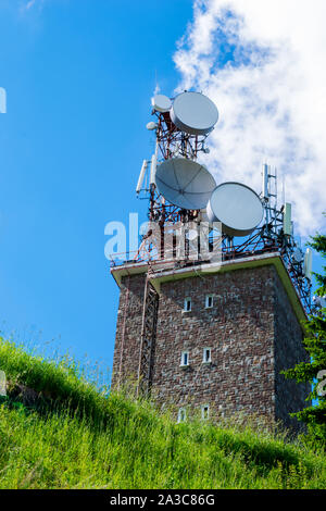 big wireless communication antennas mounted on top of utility building - Stock Photo