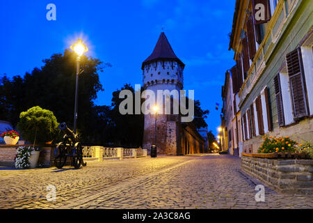 Cetatii street and Carpenters Tower (Turnul Dulgherilor), Sibiu, at blue hour, before sunrise. This brick-&-stone tower was constructed in the 14th ce - Stock Photo