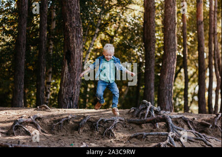 Emotional portrait of a happy and cheerful little boy, running after a friend laughing while playing on a walk in the park. Happy childhood. Summertime. Summer vacation. Positive emotions and energy. - Stock Photo