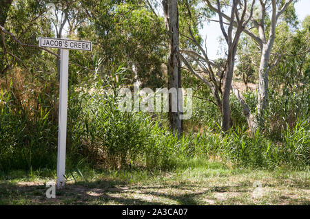 A sign, Jacobs Creek on the bank of Jacobs Creek in the grounds at the Jacobs winery in the Barossa Valley wine region in South Australia.   There are - Stock Photo