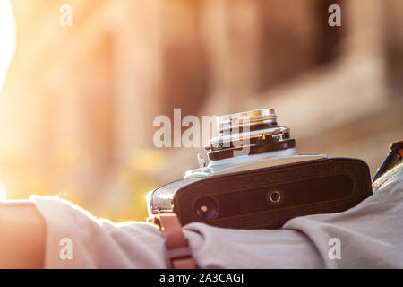 Close up shot detail of vintage camera at colosseum in Rome, Italy at sunrise. - Stock Photo