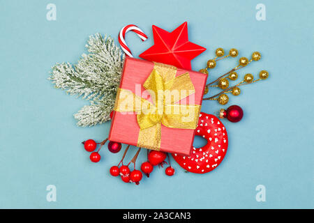 Red and blue Christmas composition. Red gift, holly berries, stars, glass baubles and green fir branch on blue background - Stock Photo