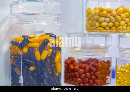Supplements and pills in clear glass bottle for sale at pharmacy drug store - Stock Photo