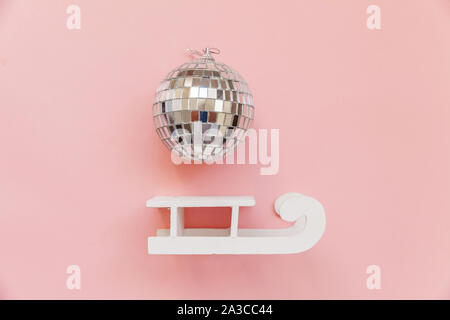 Simply minimal composition winter objects ornament ball sled isolated on pink pastel trendy background. Christmas New Year december time for celebration concept. Flat lay top view - Stock Photo