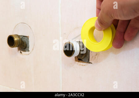 The plumber puts Teflon seam FUM tape on the thread before installing the faucet tap. - Stock Photo