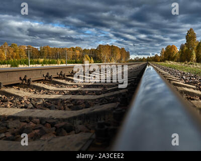 The railway road against the backdrop of a bright blue autumn sky goes to infinity. - Stock Photo