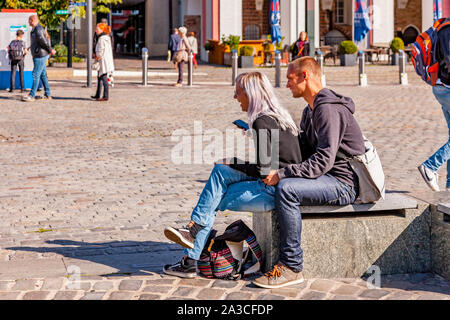 Young couple sat in The Neuer Markt (New Market) by the statues, Rostock, Germany. - Stock Photo
