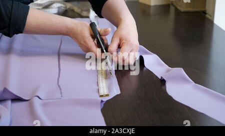 Cutting and sewing products in tailoring business. Tailor woman cutting fabric using large scissors following chalk markings of pattern, closeup hands. Dressmaker creating new clothes. - Stock Photo