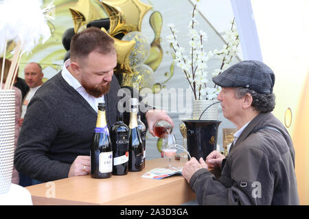 Chisinau, Moldova. 5th Oct, 2019. A staff member serves wine for a customer during the 18th edition of the National Wine Day in Chisinau, Moldova, Oct. 5, 2019. Moldova's two-day National Wine Day, aiming to promote wine production and exports, ended here on Sunday. Credit: Chen Jin/Xinhua/Alamy Live News - Stock Photo