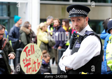 Westminster, London, UK - Monday 7th October 2019 - Met Police officer keeps an eye of the Extinction Rebellion XR climate protesters in Marsham Street directly outside the Home Office.  Photo Steven May / Alamy Live News - Stock Photo