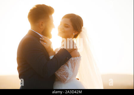 Lovely couple dressed in wedding clothes are looking and smiling at eachother. - Stock Photo