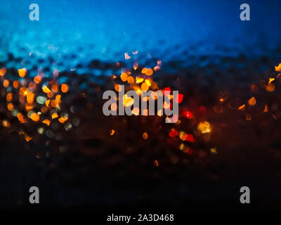 Night window with raindrops and street light of lanterns. Wet glass with multi-colored shiny drops. Blurred photo - Stock Photo