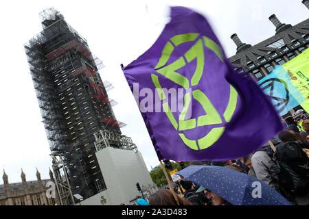 Westminster, London, UK - Monday 7th October 2019 - An Extinction Rebellion XR flag flutters in the rain on Westminster Bridge beside Big Ben.  Photo Steven May / Alamy Live News - Stock Photo
