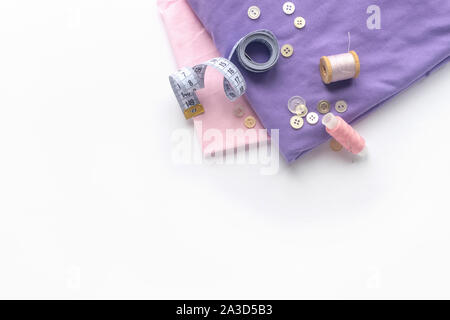 Sewing accessories and fabric on a white background. Fabric, sewing threads, needle, buttons and sewing centimeter. top view, flatlay