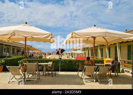A middle-aged couple sitting under a sun umbrella in the patio of a beach with rows of huts in a sunny summer day, Viareggio, Versilia, Tuscany, Italy - Stock Photo
