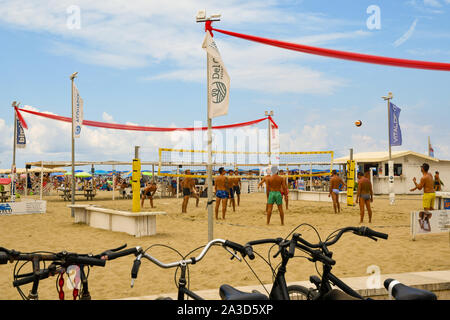 Young men playing beach volleyball on the sandy beach of Lido di Camaiore in a sunny mid-August day with parked bicycles, Versilia, Tuscany, Italy - Stock Photo
