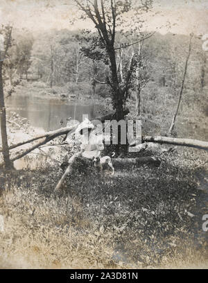 Antique c1900 photograph, woman and dog sitting on fallen tree near pond. Location unknown, probably New England, USA. SOURCE: ORIGINAL PHOTOGRAPH - Stock Photo