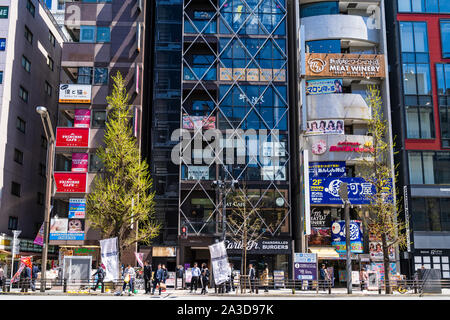 Tokyo, Akihabara. Across road view of Carls Jr Burgers US fast food outlet along with maid cafe and stores in tall buildings along the main street. - Stock Photo