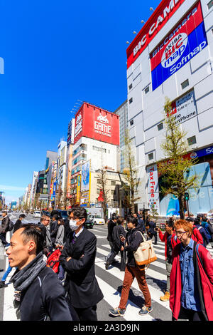 Tokyo, Akihabara. View along street of electronic and games stores, with People in foreground using a zebra crossing outside Bic Camera store. Daytime - Stock Photo