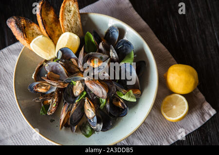 Mussels in clay bowl with lemon on wooden dark background