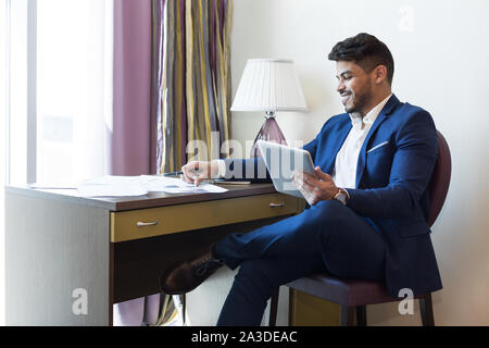 Smiling arab businessman working in hotel, using digital tablet - Stock Photo