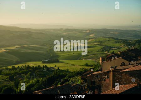 Aerial view of picturesque summer hill landscape with old buildings lush pastures and green forests in Tuscany region of Italy - Stock Photo